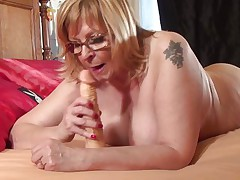 She's blonde, has big soft boobs and a pussy eager for cock and cum. Enjoy watching this mature and how she practices with her dildo, she needs to be in a good shape when a hard cock will greet her. First she sucks the dildo, then puts it between her boobs and now the blonde rubs her cunt with it, What's next?