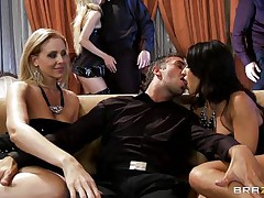 A blonde and a brunette are rubbing a guy's crotch while sitting on a couch. They pull out his cock and begin to suck it, each waiting her turn. Another dick enters the scene and the brunette goes to blow it.