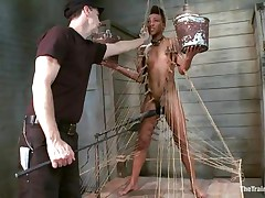 Nikki is all tied up and standing on her legs. Filled with clothespins and strings, she has to be careful and not to drop the two buckets she`s holding, while a big vibrator makes sensations on her wet cunt. She gets all whipped for being such a bad ebony girl. Her executor will take very good care of her!