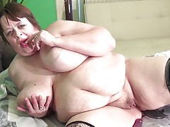 Marjan is on the bed, making the cameraman hot the way she plays with her massive melons. It's not too long before she oils her giant jugs and gets out a dildo, sliding it between her tits. She sucks on it seductively, making the cameraman moan with lust. She continues to tease him this way.