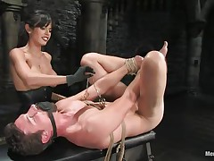 She has tied his balls with a rope and she has tied the other end of the rope to a bucket. It means that he cannot move without pain in his balls. He is commanding her to suck her pussy and lick her ass. Then she makes him lie on the table as she squeezes his balls and hurt him as badly as she can.